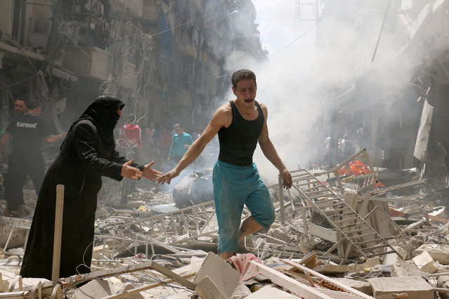 People walk amid the rubble of destroyed buildings following a reported air strike on the rebel-held neighbourhood of al-Kalasa in the northern Syrian city of Aleppo, on April 28, 2016. The death toll from an upsurge of fighting in Syria's second city Aleppo rose despite a plea by the UN envoy for the warring sides to respect a February ceasefire. (Photo by Ameer Alhalbi/AFP Photo)
