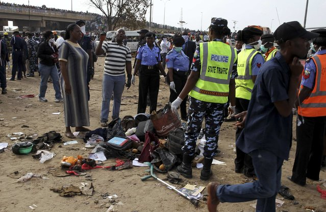Police officers gather the belongings of victims at the scene of a bomb explosion at Nyanyan, in Abuja April 14, 2014. (Photo by Afolabi Sotunde/Reuters)