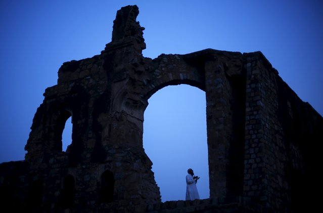 A Muslim man calls for the evening prayer after having his iftar (breaking of fast) meal during the holy month of Ramadan at the ruins of the Feroz Shah Kotla mosque in New Delhi, India, June 28, 2015. (Photo by Adnan Abidi/Reuters)