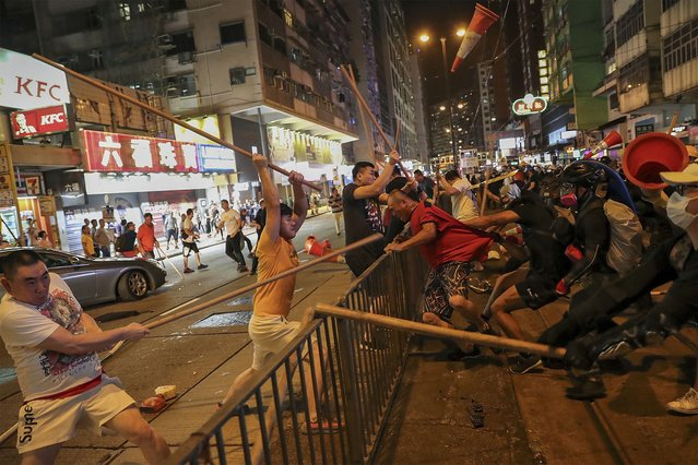 "In this Monday, August 5, 2019, photo, protesters wearing black shirt, right, fight with a group of men wielding wooden poles on a street during the anti-extradition bill protest at a neighborhood in Hong Kong. China warned Tuesday, Aug. 6 that it will be ""only a matter of time"" before it punishes those behind two months of pro-democracy protests in Hong Kong that have increasingly devolved into violent clashes with law enforcement. (Photo by AP Photo/Stringer)"