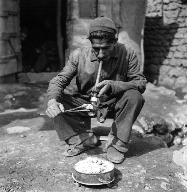 1955:  A man smoking opium in a village in Iran