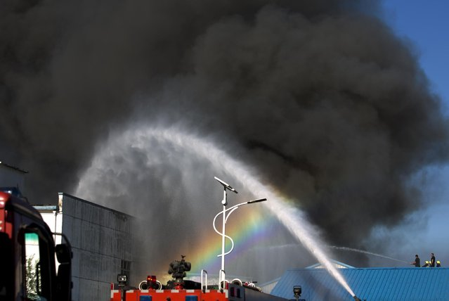 A rainbow appears on the water splayed from a fire engine as firemen extinguish a fire on a lumberyard at the south side of Beijing, China, Tuesday, June 30, 2015. (Photo by Andy Wong/AP Photo)