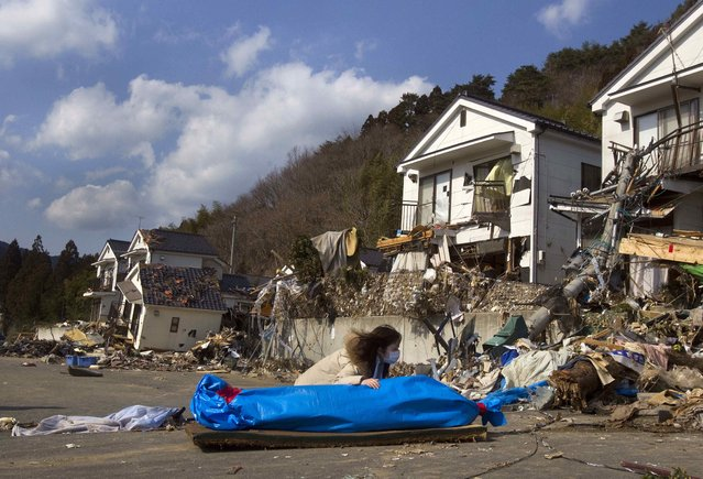 Tayo Kitamura, 40, kneels in the street to caress and talk to the wrapped body of her mother Kuniko Kitamura, 69, after Japanese firemen discovered the dead woman inside the ruins of her home in Onagawa, northeastern Japan Saturday, March 19, 2011. (Photo by David Guttenfelder/AP Photo)
