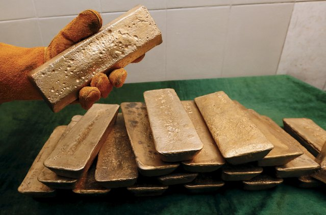 A melter places an ingot of 92.96 percent pure gold at a procession plant of the Olimpiada gold operation, owned by Polyus Gold International company, in Krasnoyarsk region, Eastern Siberia, Russia, June 30, 2015. (Photo by Ilya Naymushin/Reuters)