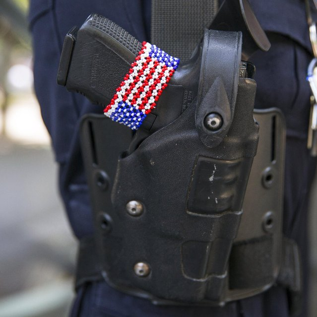 A bracelet in the design of the U.S. flag is seen on the gun of a police officer in Manhattan, New York, July 3, 2015, ahead of the Fourth of July holiday. (Photo by Andrew Kelly/Reuters)