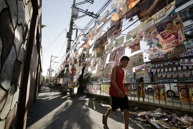 A man walks past layers of election campaign posters in Manila, Philippines, Friday, May 6, 2016. Campaign materials can be seen in almost every corner of the city as the country as it gears up for the presidential elections on Monday. (Photo by Aaron Favila/AP Photo)