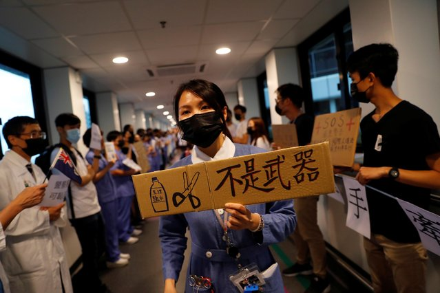 "A healthcare staff holds a placard which reads ""Saline water and scissors are not weapons"", as other staff members participate in a human chain to protest against the police brutality during the anti extradition bill protests, at Queen Mary Hospital, in Hong Kong, China, September 2, 2019. (Photo by Anushree Fadnavis/Reuters)"