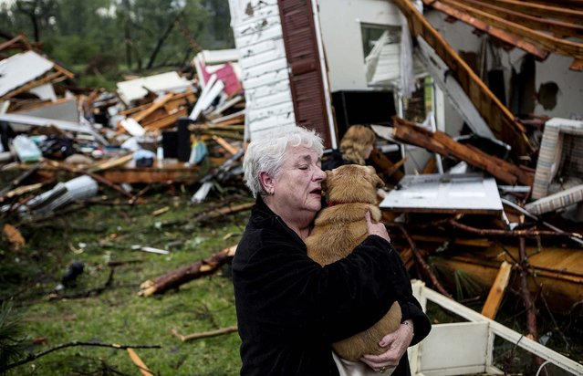 Constance Lambert embraces her dog after finding it alive when returning to her destroyed home in Tupelo, Miss., Monday, April 28, 2014. Lambert was at an event away from her home when the tornado struck and rushed back to check on her pets. (Photo by Brad Vest/AP Photo/The Commercial Appeal)