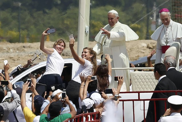 """Pope Francis waves to the crowd of faithfuls upon his arrival at Parque Samanes where he will celebrate mass in Guayaquil, Ecuador, July 6, 2015. Camped on streets with sleeping bags and stocked with food supplies, thousands of excited Ecuadoreans congregated in the coastal city of Guayaquil on Monday for Pope Francis' first mass of his """"homecoming"""" tour of South America. (Photo by Jose Miguel Gomez/Reuters)"""