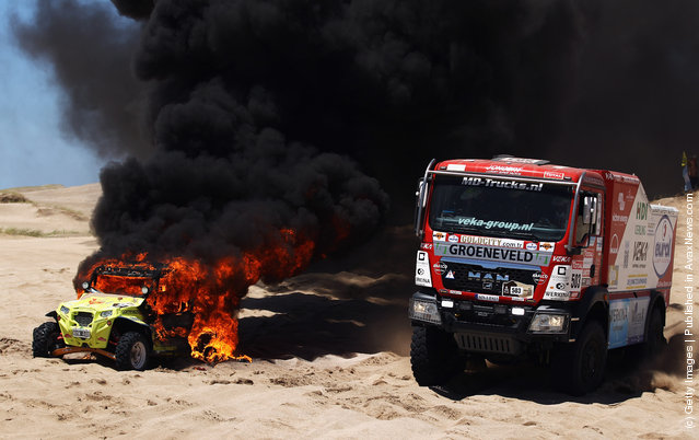 Franz Echter of Germany drives around the burning car of Jose Antonio Blangion of Argentina during stage one of the 2012 Dakar Rally