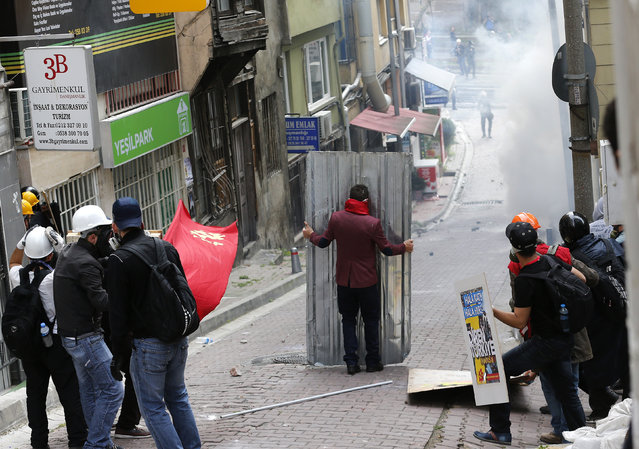 Protesters shield themselves as riot police fires tear gas during a May Day demonstration in Istanbul May 1, 2014. Turkish police fired water cannon and tear gas on Thursday to prevent hundreds of protesters from defying a ban on May Day rallies and reaching Istanbul's central Taksim Square, the focal point of weeks of protests last summer. (Photo by Murad Sezer/Reuters)
