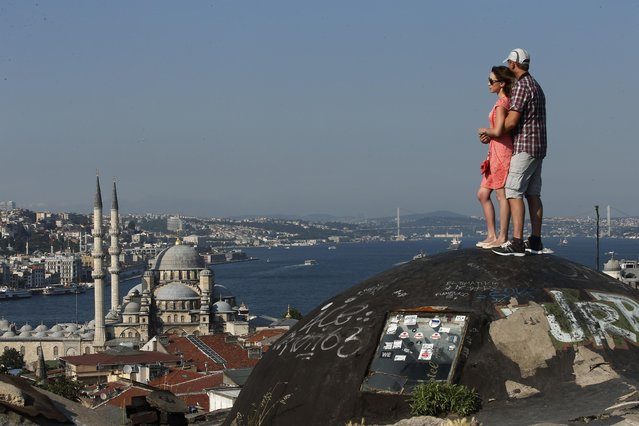 A couple view Istanbul's skyline with the New Mosque, left, and the Bosporus, Thursday, July 9, 2015. (Photo by Emrah Gurel/AP Photo)