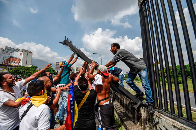 Demonstrators try to tear down a fence at the La Carlota air base during a rally against Venezuelan President Nicolas Maduro, in Caracas on April 19, 2017. (Photo by Juan Barreto/AFP Photo)