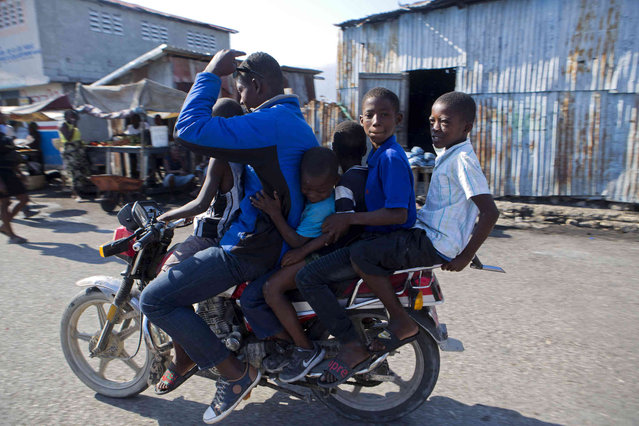 A moto-taxi driver carries five youths on his motorcycle through the Cite Soleil area of Port-au-Prince, Haiti, Sunday, March 17, 2019. (Photo by Dieu Nalio Chery/AP Photo)