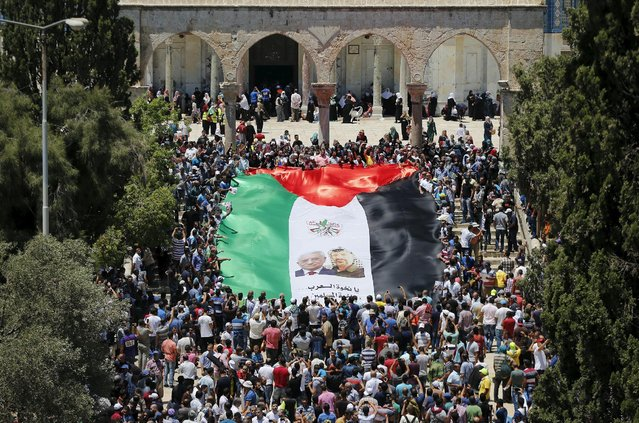 Palestinians hold a large flag depicting President Mahmoud Abbas (L) and late Palestinian leader Yasser Arafat during a rally marking the annual al-Quds Day, or Jerusalem Day, on the fourth Friday of the holy month of Ramadan, at the compound known to Muslims as the Noble Sanctuary and to Jews as Temple Mount, in Jerusalem's Old City July 10, 2015. (Photo by Ammar Awad/Reuters)