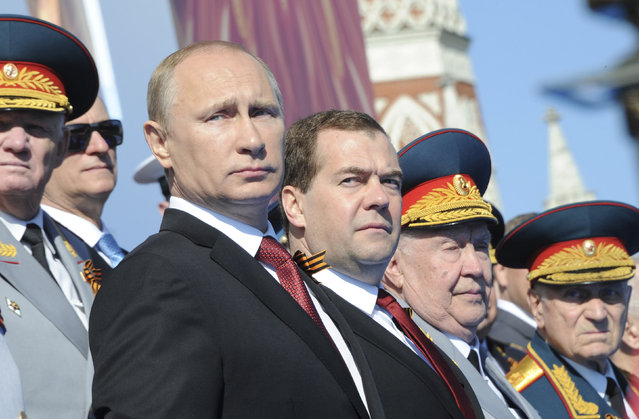 Russia's President Vladimir Putin (front L) and Prime Minister Dmitry Medvedev (C) watch the Victory Day parade in Moscow's Red Square May 9, 2014. (Photo by Mikhail Klimentyev/Reuters)