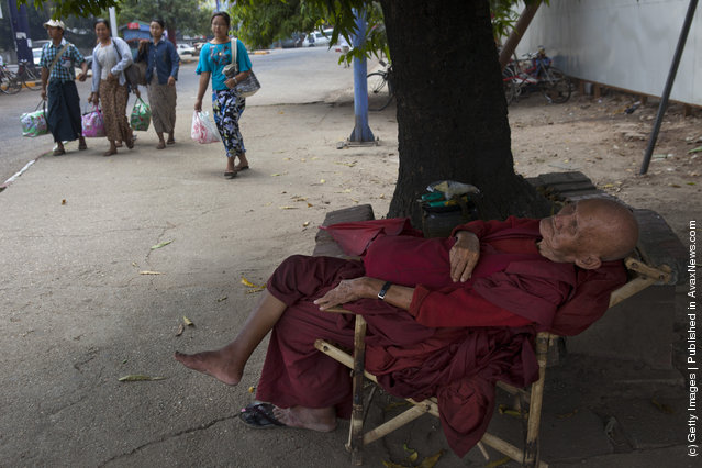 A Burmese monk sleeps under the shade of a tree during a hot afternoon