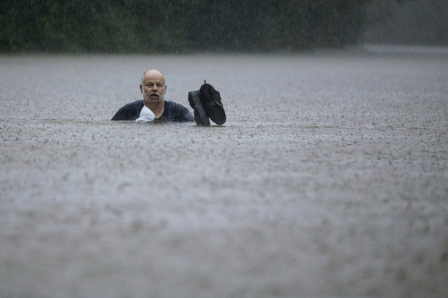 A man wades out through floodwaters caused by heavy rain spawned by Tropical Depression Imelda inundated the area on Thursday, September 19, 2019, in Patton Village, Texas. (Photo by Brett Coomer/Houston Chronicle via AP Photo)