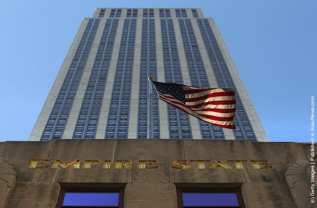 A flag blows in the wind in front of the Empire State Building