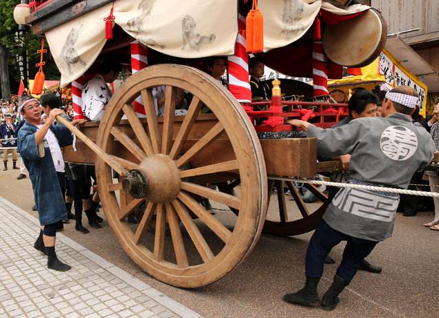 Festival goers pull huge cart wheel of historical Japanese figure paper doll carry during the Mikuini annual festival on May 20, 2014 in Sakai, Japan. The annual festival takes place from May 19-21 and is attended by thousands of visitors. During the festival people dressed in traditional Japanese costumes pull carts carrying 6 meter high dolls of Japanese historical figures through the narrow streets. The origins of the festival are unclear but its history can be traced back more than 250 years. (Photo by Buddhika Weerasinghe/Getty Images)