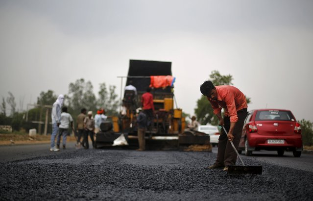 A labourer works at the construction site of the Delhi-Jaipur national highway in Manesar in the northern state of Haryana, India, July 9, 2015. (Photo by Adnan Abidi/Reuters)