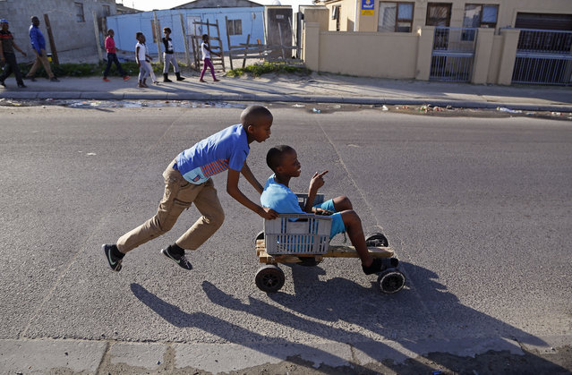 In this Monday, July 6, 2015 photo, a child pushes a friend in a home-made go-kart in the Khayelitsha township near Cape Town, South Africa. The vehicle was built with recycled wood, plastic containers and old nails. (Photo by Schalk van Zuydam/AP Photo)