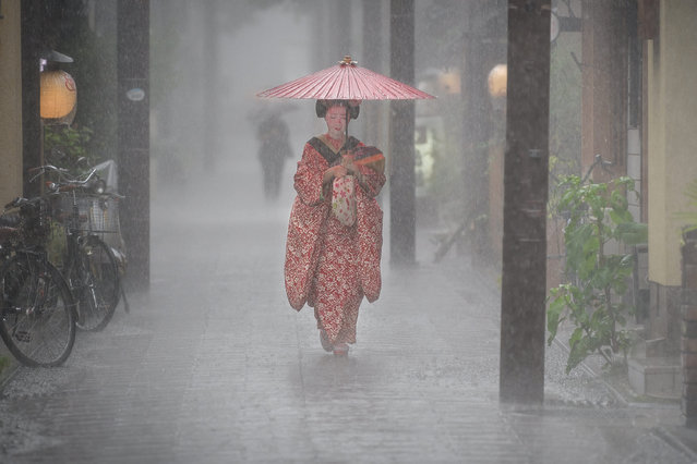 """Pouring Down"". Patrick Hochner captures a geisha apprentice with a waxed silk umbrella in Kyoto, Japan, in this shortlisted shot. (Photo by Patrick Hochner/2019 Weather Photographer of the Year/RMetS)"