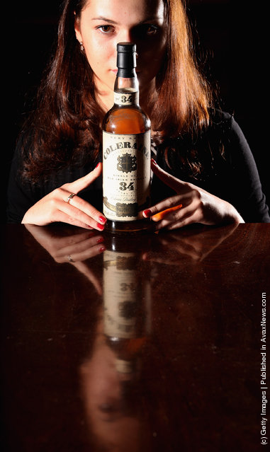 Victoria Kasperovich, an employee at McTear's Auctioneers, views a bottle of Coleraine Single Malt Old Irish whiskey