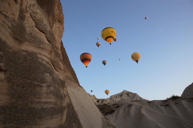 Hot air balloons glide over Goreme district during early morning at the historical Cappadocia region, located in Central Anatolia's Nevsehir province, Turkey on November 10, 2019. Cappadocia is preserved as a UNESCO World Heritage site and is famous for its chimney rocks, hot air balloon trips, underground cities and boutique hotels carved into rocks. In Turkey's one of the most important tourism regions Cappadocia, local and foreign tourists get the chance of enjoying the scenery participating air balloon tours in the early hours of the morning. (Photo by Behcet Alkan/Anadolu Agency via Getty Images)