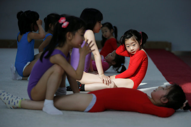Girls practice sit-ups during gymnastics lessons at the Shanghai Yangpu Youth Amateur Athletic School in Shanghai, China, on May 4, 2016. (Photo by Aly Song/Reuters)