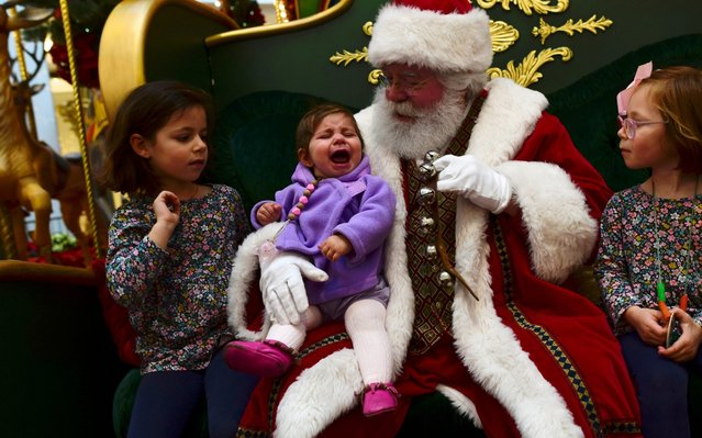(C) Tatum Solomon, 10 months old, cries while being held by Santa Claus, while sisters (L) Bennet, 6, and (R) Campbell, 4, look on as pre-Thanksgiving and Christmas holiday shopping accelerates at the King of Prussia Mall in King of Prussia, Pennsylvania, U.S. November 22, 2019. (Photo by Mark Makela/Reuters)