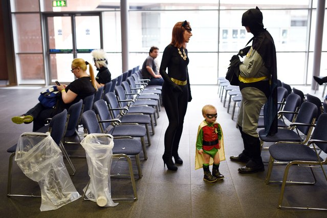 Cosplayers Natasha (C) and Conor Lindop (R), dressed as characters from the Batman franchise attend the second day of the MCM Comic Con in the Manchester Central exhibition venue with their son Dylan, aged 2, dressed as Robin in the Manchester Central exhibition venue in Manchester, north west England on July 26, 2015. (Photo by Oli Scarff/AFP Photo)