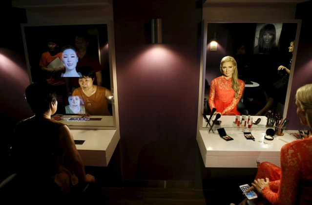 A woman looks at a mirror next to the wax figure of Paris Hilton at Grevin Wax Museum in central Seoul, South Korea, July 30, 2015. (Photo by Kim Hong-Ji/Reuters)