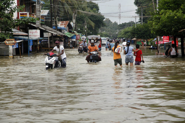 Local residents wade through a flooded road in Bago, 80 kilometers (50 miles) northeast of Yangon, Myanmar, Saturday, August 1, 2015. Myanmar's president has declared several regions of the country to be disaster zones, as forecasts of heavy rain for the next few days have heightened fears that already dire flooding in many parts of the country will get worse. (Photo by Khin Maung Win/AP Photo)