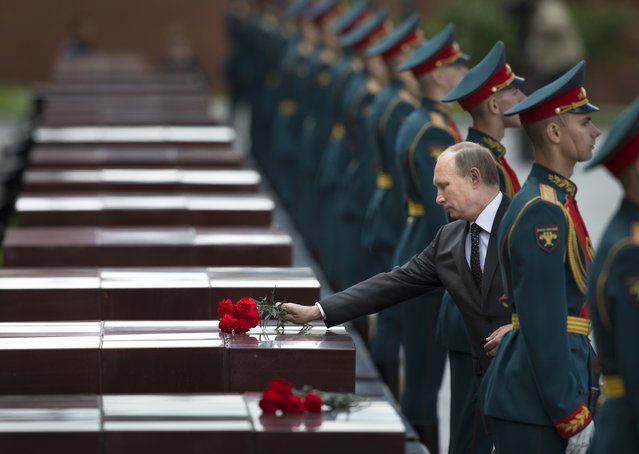 Russian Vladimir Putin, second right, takes part in a wreath laying ceremony at the Tomb of the Unknown Soldier outside Moscow's Kremlin Wall, in Moscow, Russia, Sunday, June 22, 2014,  to mark the 73rd anniversary of the Nazi invasion of the Soviet Union. (Photo by Alexander Zemlianichenko/AP Photo)