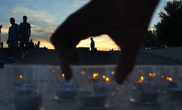 """The scene as people light candles to form the letters into the words, """"So All Can Vote"""" to support Voting Rights during a vigil on June 24, 2014 in Washington, DC. The vigil was a memorial to Andrew Goodman, James Chaney and Michael Schwerner, who were killed in 1964 by the KKK in Mississippi. The vigil included a display of 3,000 candles at the base of the Lincoln Memorial near the reflecting pool. Bend the Arc: A Jewish Partnership for Justice organization sponsored the memorial event on the 50th anniversary of their  activist murders. (Photo by Michel du Cille/The Washington Post)"""