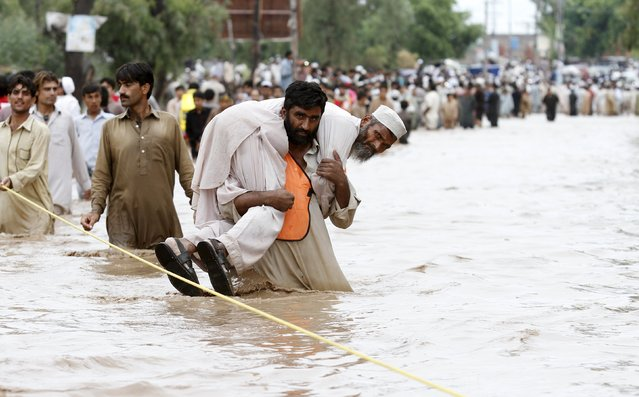 Residents walk in floodwater caused by heavy rainfalls in Peshawar, Pakistan, July 26, 2015. Flash flooding caused by torrential monsoon rains has killed at least 28 in Pakistan and affected hundreds of thousands of people, according to aid agencies, with further downpours expected in the coming days. (Photo by Fayaz Aziz/Reuters)