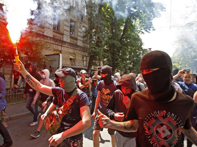 A man carries a smoke flare as far-right activists march during the Gay Pride parade on June 12, 2016 in Kiev. More than 700 gay rights activists marched through central Kiev on June 12 amid a massive police presence for the third such gay pride event in the ex-Soviet country where homophobia remains widespread. The June 12 march was the first ever gay pride rally to be held in central Kiev, prompting an unprecedented security operation with several thousand police and National Guard officers lining the route during the event, which lasted around 20 minutes. (Photo by Yuriy Kirnichny/AFP Photo)
