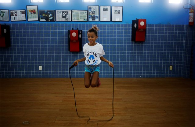 A girl jumps on a rope during an exercise session at a boxing school, in the Mare favela of Rio de Janeiro. (Photo by Nacho Doce/Reuters)