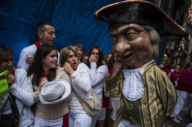 "People look at a ""Cabezudo"", one member of  San Fermin Comparsa Group, during the San Fermin festival, in Pamplona, Spain, Monday, July 7, 2014. Revelers from around the world arrive to Pamplona every year to take part in some of the eight days of the running of the bulls glorified by Ernest Hemingway's 1926 novel ""The Sun Also Rises"". (Photo by Alvaro Barrientos/AP Photo)"