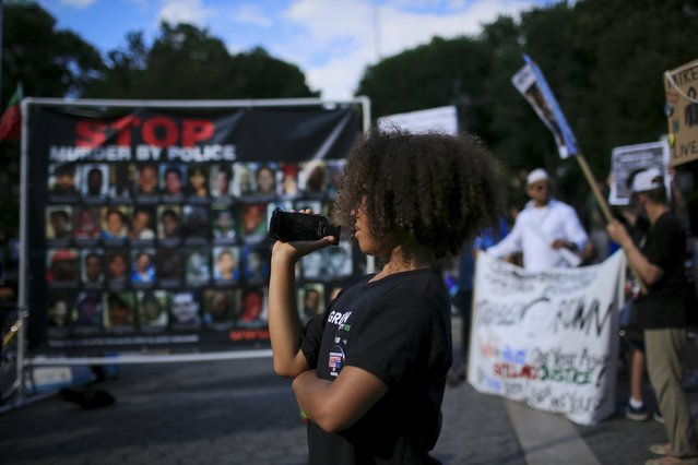 A child records protesters while they take part in a small rally at Union Square marking the first anniversary of the death of Michael Brown, an unarmed black teenager shot dead by a white police officer in Ferguson, Missouri a year ago, in New York August 9, 2015. (Photo by Eduardo Munoz/Reuters)
