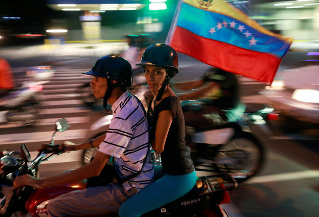 Opposition supporters ride on a motorcycle after an unofficial plebiscite against President Nicolas Maduro's government and his plan to rewrite the constitution, in Caracas, Venezuela July 16, 2017. (Photo by Marco Bello/Reuters)