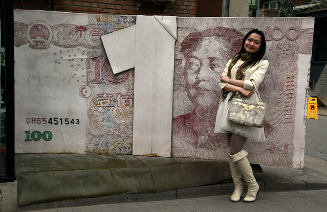 In this March 15, 2012 file photo, a Chinese woman poses for photos near a sculpture depicting a Chinese yuan note at an art district in Beijing, China. China devalued its tightly controlled currency on Tuesday, August 11,2015,  following a slump in trade, triggering the yuan's biggest one-day decline in a decade. The central bank said the yuan's 1.3 percent fall was due to a change aimed at making its exchange rate controls more market-oriented. But any change raises the risk of tensions with China's trading partners. (Photo by Ng Han Guan/AP Photo)