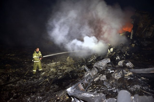 A firefighter sprays water to extinguish a fire, on July 17, 2014, amongst the wreckages of the malaysian airliner carrying 295 people from Amsterdam to Kuala Lumpur after it crashed, near the town of Shaktarsk, in rebel-held east Ukraine. Ukrainian President Petro Poroshenko said on Thursday that the Malaysia Airlines jet that crashed over rebel-held eastern Ukraine may have been shot down. (Photo by Alexander Khudoteply/AFP Photo)