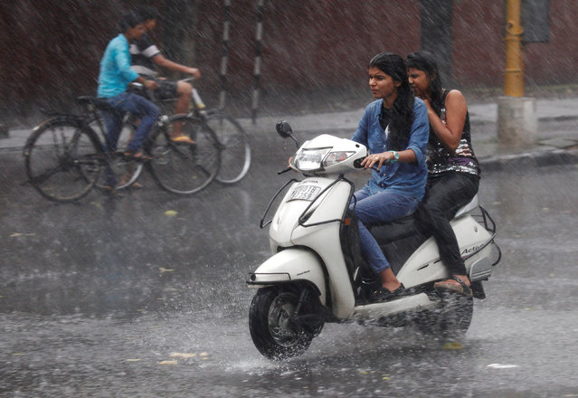 People commute during a heavy rain shower in Chandigarh, India, June 22, 2016. (Photo by Ajay Verma/Reuters)