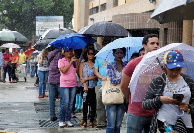 People gather outside a validation center during Venezuela's CNE second phase of verifying signatures for a recall referendum against President Maduro, in Caracas, Venezuela, June 24, 2016. (Photo by Mariana Bazo/Reuters)