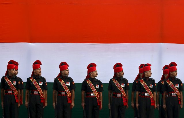 Indian soldiers stand guard in front of an India's national flag tri-colours during the full-dress rehearsal for India's Independence Day celebrations at the historic Red Fort in Delhi, India, August 13, 2015. (Photo by Adnan Abidi/Reuters)