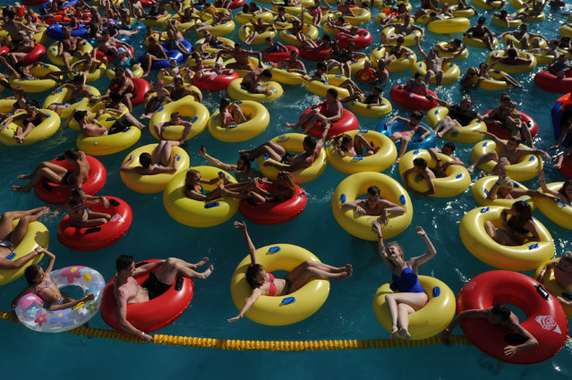 People cool off in a pool at an aqua park in Minsk, Belarus on August 1, 2017, as temperatures reached 30 degrees Celsius. (Photo by Sergei Gapon/AFP Photo)