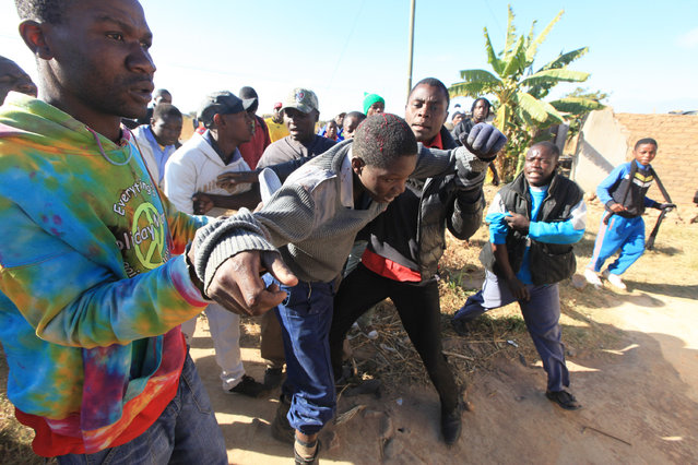 A police officer is assisted after being assaulted by angry protesters in Harare, Monday, July, 4, 2016. (Photo by Tsvangirayi Mukwazhi/AP Photo)