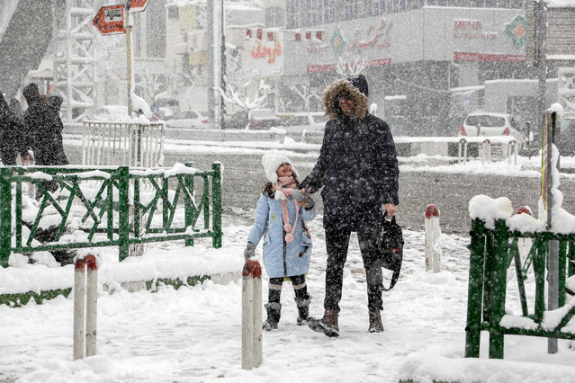 A man and a girl walk through a snow blizzard along a road in the Iranian capital Tehran on January 19, 2020. (Photo by Atta Kenare/AFP Photo)